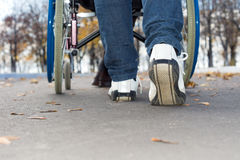 Person pushing a wheelchair down the street Stock Images