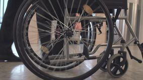 Person Pushing Wheelchair. Person pushing empty wheelchair in the airport or hospital, close up slow motion shot of rolling wheels. Medicine, recovery and stock video footage