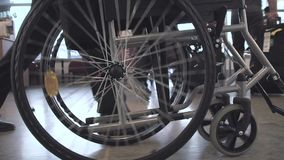 Person Pushing Wheelchair. Person pushing empty wheelchair in the airport or hospital, close up slow motion shot of rolling wheels. Medicine, recovery and stock video