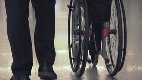 Person Pushing Wheelchair. Person pushing empty wheelchair in the airport or hospital, close up slow motion shot of rolling wheels. Medicine, recovery and stock footage