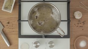Person puts black pepper in boiling water in metal pan on kitchen. Person puts black pepper in boiling water in metal pan on bright kitchen stock video