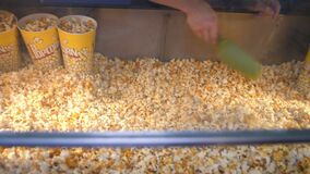 Person puts bucket and mixes popcorn on display in cafe