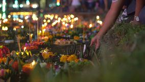 Person puts a krathong with a burning candle in a water full of floating krathongs. Celebrating a traditional Thai. Holiday - Loy Krathong stock video