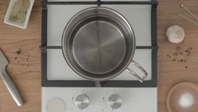 Person puts metal pan with water on gas stove and turns it on stock footage