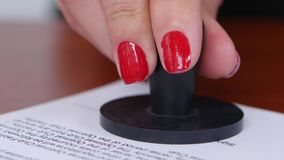 Person puts a stamp on the document. Close up stock video