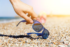 Person puts sunglasses on seashore Stock Images