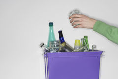 Person putting jar into recycling container filled with empty glass vessels royalty free stock photos