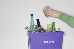 Person putting jar into recycling container filled with empty glass vessels Stock Photo