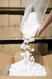 Person putting packing peanuts in box Royalty Free Stock Image