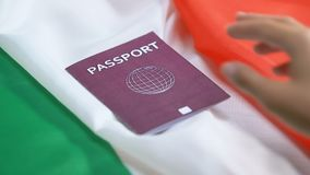 Person putting red passport on Italian flag background, citizenship status. Stock footage stock video