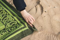 Person putting a towel on the beach. Summer concept. Close-up of a hand and a towel on the beach royalty free stock photography