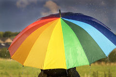 A person with rainbow colored umbrella in the rain Stock Photos