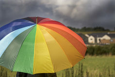 A person with rainbow colored umbrella under storm clouds Stock Photos