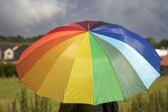 A person with rainbow colored umbrella under storm clouds Royalty Free Stock Images