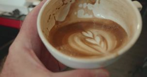 Person raises half full cup of coffee to drink stock video