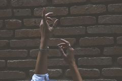 Person Raising Its Two Hand Beside Brown Brick Wall Royalty Free Stock Images