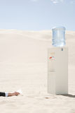 Person reaching for water cooler in desert Royalty Free Stock Photos