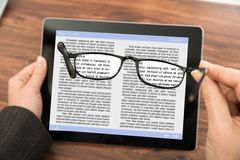 Person reading e-book with spectacles. Close-up Of Person Reading E-book On Digital Tablet With Spectacles Royalty Free Stock Images