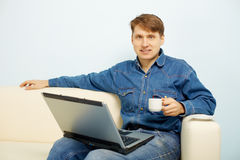 Person reads news in Internet at home on sofa Stock Images