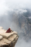 Person in Red and Black Blanket Sitting on Cliff Stock Photo