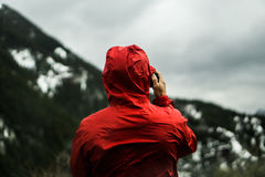 Person in Red Hoodie Taking a Photo in Front of Mountain Stock Images