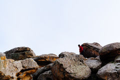 Person in Red Jacket Standing on the Rock Royalty Free Stock Images