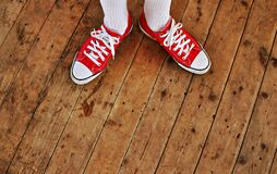 Person in Red Low Tops in Brown Wooden Floor Stock Image