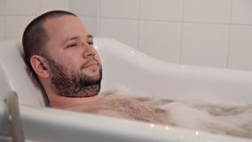 A person relaxing in a beauty salon. The man lies in the bathroom with hydro massage and healing oils. Health, beauty stock footage