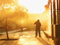 Person removes garbage on the street. Against the background of light from the rising sun, a person removes garbage on the street Royalty Free Stock Images