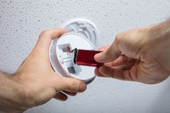 Free Person Removing Battery From Smoke Detector Stock Photography - 103340312