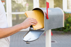 Person Removing Letters From Mailbox. Close-up Of Person Removing Yellow Letters From Mailbox stock images