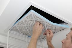 Man Removing Dirty Air Filter. Person removing an old dirty air filter from a ceiling intake vent of a home HVAC system. Unclean gray square furnace air filter stock image