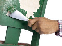 Person removing paint. From old green chair Royalty Free Stock Images