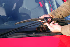 Person repairing windshield wiper. A close up of a person repairing or replacing a windscreen or windshield wiper on a car Stock Images