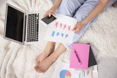Person sitting on bed with laptop Royalty Free Stock Photography