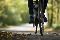 Person riding a bicycle along a fall road. With dried autumn leaves scattered on the asphalt in a low angle view of the feet and wheels Stock Photo