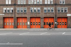 Person Riding Bicycle in Front of Brown Orange Brick Building Royalty Free Stock Photography