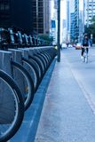 Person on a bike riding down a city street in Toronto near a bik. Person riding a bike on a busy city street with cars and skyscrapers in the background and a Royalty Free Stock Images