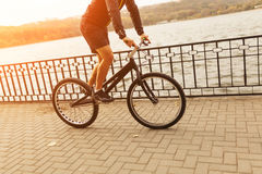 Person riding a bike on esplanade. An unrecognizable person riding a trial bike on the esplanade in the city. Horizontal outdoors shot Royalty Free Stock Photos