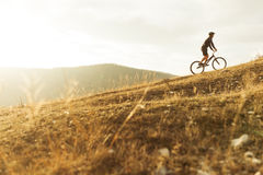 Person riding bike in hills. Side view of an unrecognizable person riding a trial bike in the hills. Horizontal outdoors shot Royalty Free Stock Image