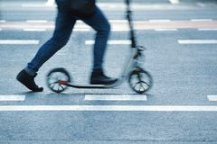 Person riding a scooter in the street throw a pedestrian crossing. Empty copy space for Editor`s text stock photography