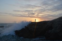 Person on rocky coastline at sunset Royalty Free Stock Photography