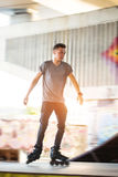 Person on rollerblades. Young man on blurred background. Youth and courage Stock Image