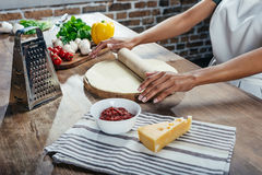 Person rolling dough while cooking pizza stock photos
