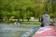 Person on roof of red white and blue boat with rowing team and trees in background. Retired lonely man sat on bow of boat wearing grey jumper with gray hair stock photos