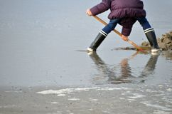 Person in rubber boots on beach Stock Image