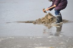 Person in rubber boots on beach Royalty Free Stock Images