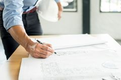 Person`s engineer Hand Drawing Plan On Blue Print with architect equipment, Architects working at the table.  royalty free stock image