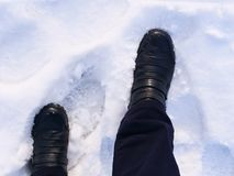 Person`s feet in leather boots walking in the snow. In winter stock photography