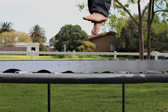 A person`s feet visible above a trampoline. A person`s feet, mid-bounce above a trampoline, background of suburbia stock photos